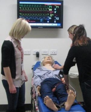 Nursing students and simulator manikin