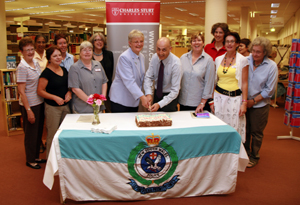 Shirley Oakley and Tony Stephenson cut the cake surrounded by Bathurst library staff