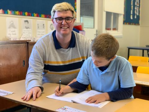 Ed Smith pictured helping one of his students with class work
