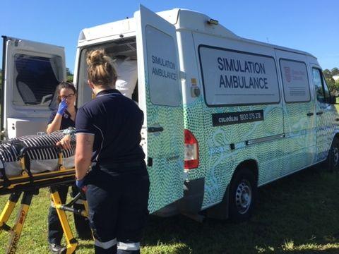 Students using ambulance simulation vehicle with Indigenous artwork